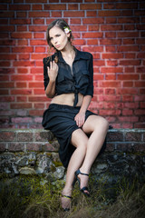 Charming young woman in black dress sitting on brick wall
