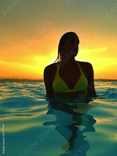 woman in pool at sunset