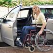 Frau mit Rollstuhl steigt in Auto
