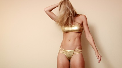 Dance woman moving faast in gold bikini showing body