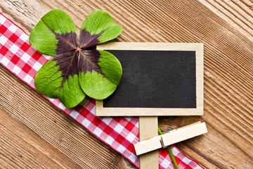 Holzhintergrund mit Tafel und vierblättrigem Kleeblatt