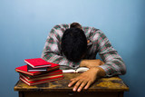 Young man sleeping at desk after studying