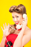 Pin-up girl talking on retro telephone on yellow background