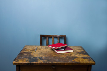 Old wooden desk and chair with books and a pen