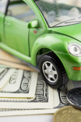 Toy car and money over white  Rent, buy or insurance car concept