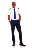 african airline pilot standing over white background