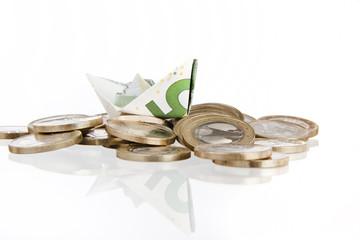 Münzgeld mit 5 Euro Papierschiff vor weissem Hintergrund