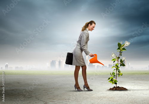 Business woman watering monet tree