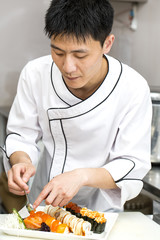 Japanese chef with a plate of sushi