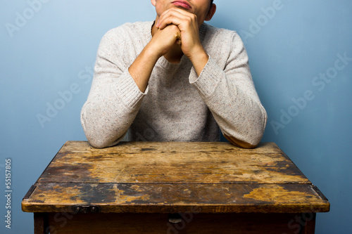 Man sitting at desk deep in thought