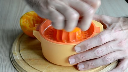 Un hombre preparando un zumo de naranja