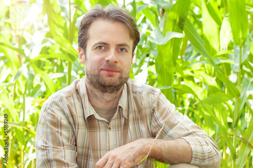 Happy smiling caucasian farmer in front of corn field