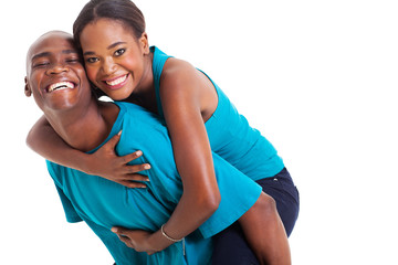 african woman enjoying piggyback ride on boyfriends back