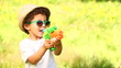 Little boy smiling while using water pistol
