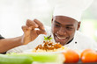 Afro American chef in restaurant kitchen garnishing pasta dish