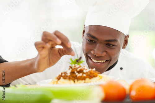 Afro American chef in restaurant kitchen garnishing pasta dish - 55161234