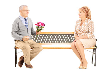 Mature gentleman giving a flower bouquet to a woman and sitting