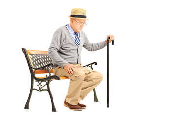 Senior man with a cane sitting on a bench