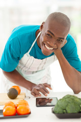 afro american man searching recipe on tablet computer