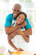 african couple hugging in home kitchen