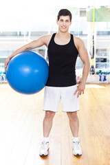 Smiling handsome man with Pilates ball