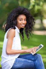Outdoor portrait of a teenage black girl using a tactile tablet
