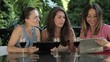 Three female friends with tablet computer in outdoors restaurant