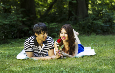 Young Adult Couple Enjoy Looking at Single Red Rose
