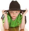 Boy green shirt cowboy hat look serious lay