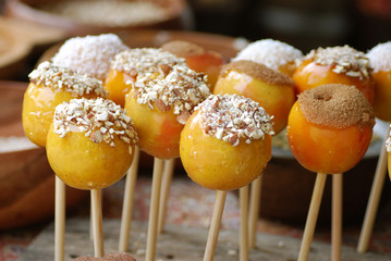 brown toffee apples with nuts and sugar toppings