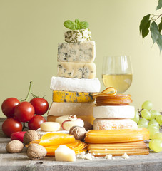 Pile of cheese many various types with wine grapes and nuts