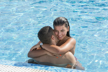 Young couple enjoying in swimming pool on a hot summer day