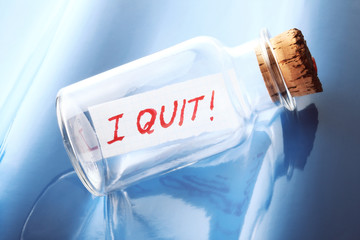 "A concept of a bottle with a message ""I quit"""