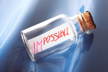 "Psychology concept of a bottle with a message ""impossible"""