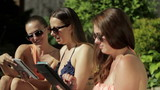 Three female friends with tablet computer outdoors