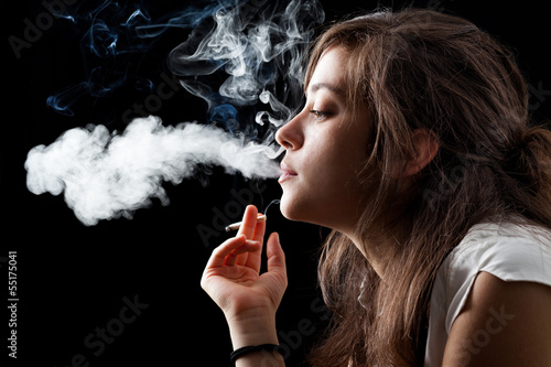 Woman Smoking a Cigarette on Black Background - 55175041