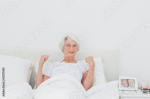 Woman stretching and raising arms in bed