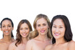 Smiling nude models posing in a line with brunette on background