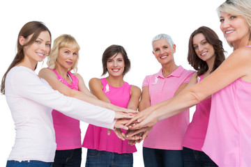 Cheerful women posing in circle holding hands looking at camera