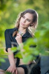 Cute woman in black dress and high heels sitting on brick wall