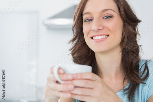 Cheerful brunette holding cup of coffee