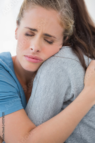 Woman taking her sad friend in her arms
