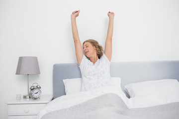 Well rested blonde woman stretching after waking up in bed