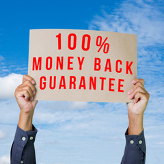 Hands holding brown paper with money back guarantee