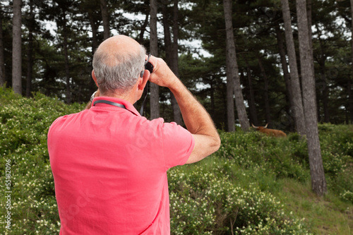 Senior man using binoculars outdoors. Watching scottish highland
