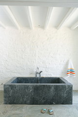 Square shaped marble bathtub in bathroom