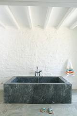 Square shaped marble bathtub in bathroom