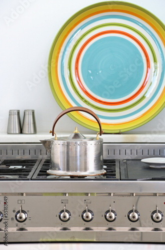 Modern stove detail with kettle and decorative plate