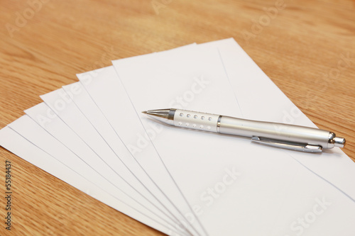 envelopes with a pen on a table