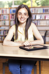 Smiling student using a tablet computer in a university library